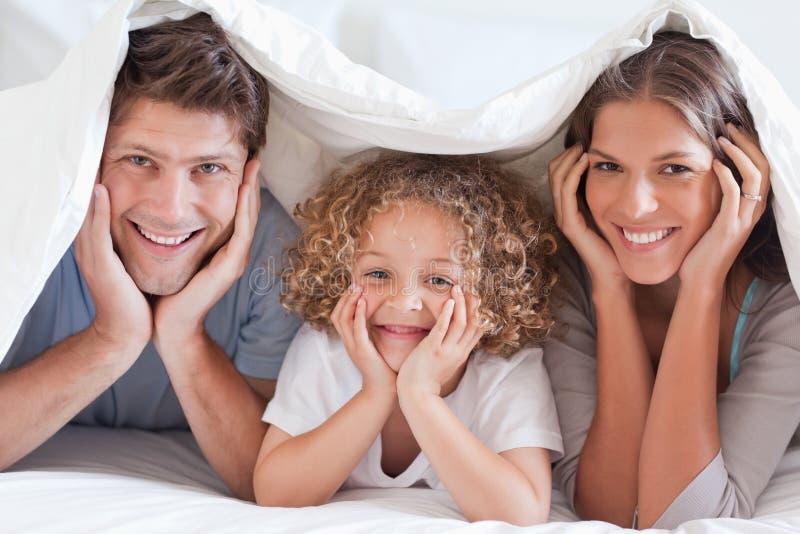 Family posing under a duvet royalty free stock photo