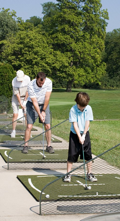 Family Practicing Golf. Three Generations Practicing Their Golf Together stock image