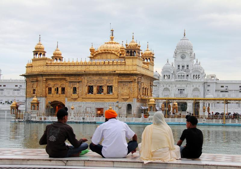 A family praying in front of golden temple royalty free stock images