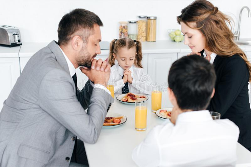 family praying at table during breakfast in kitchen stock photos