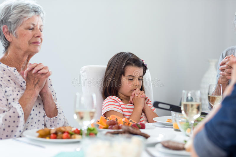 Family praying together before meal royalty free stock image