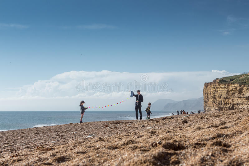 Family prepare to fly a kite on sunny beach royalty free stock images