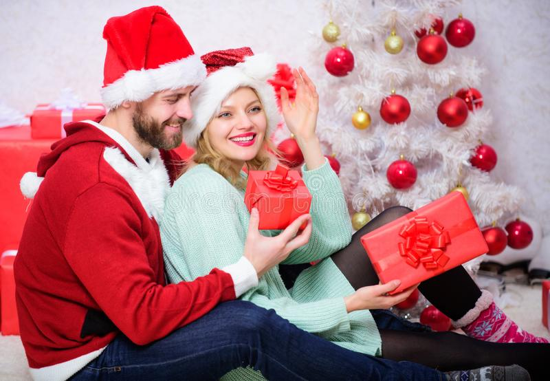 Family prepared christmas gifts. Loving couple cuddle smiling while unpacking gifts with christmas tree background stock images