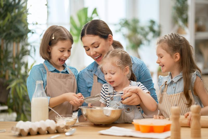 Family are preparing bakery together. Happy loving family are preparing bakery together. Mother and children daughters girls are cooking cookies and having fun stock image