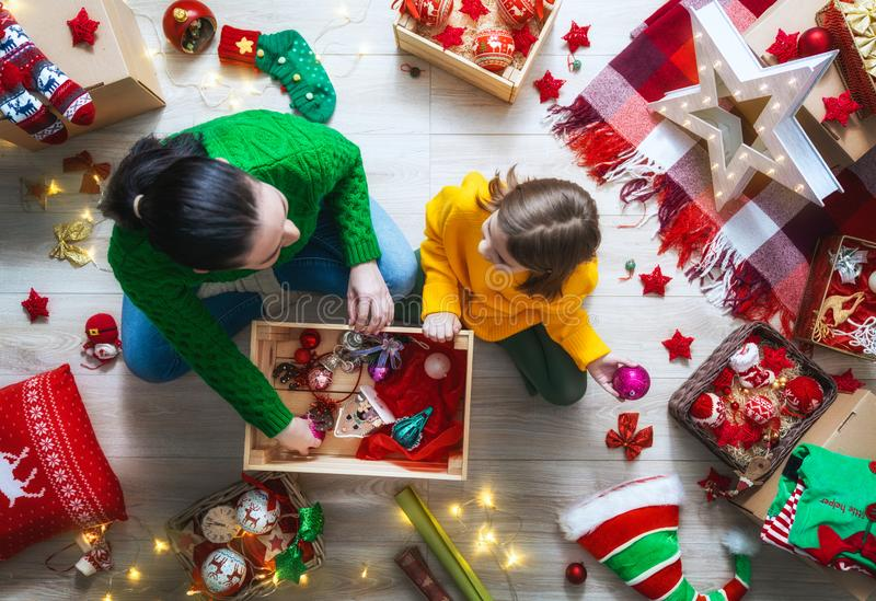 Family preparing for Christmas. Happy family preparing for Christmas. Mother and her daughter decorating home for holidays royalty free stock photography