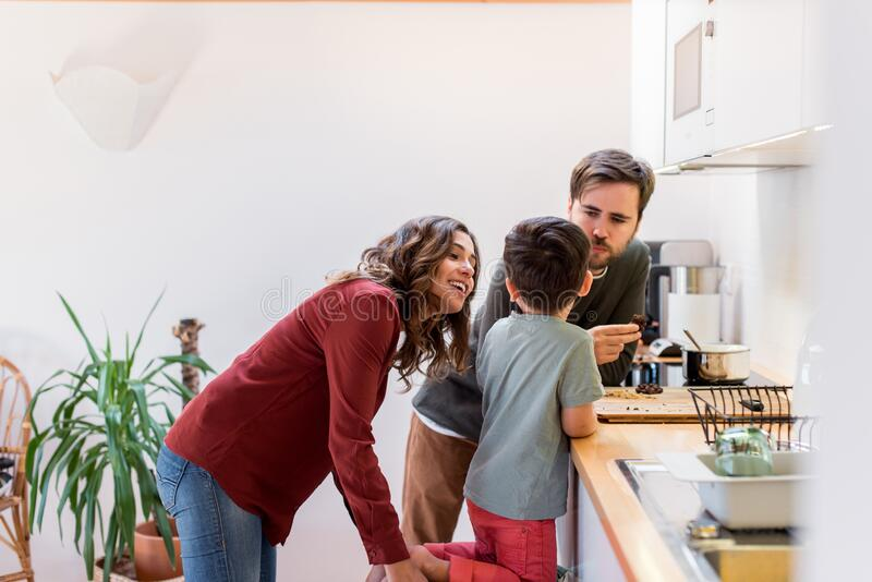 Family preparing and eating peanut chocolate cookies at home stock image
