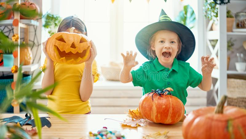 Family preparing for Halloween. Cute little children girls with carving pumpkin. Happy family preparing for Halloween royalty free stock photo