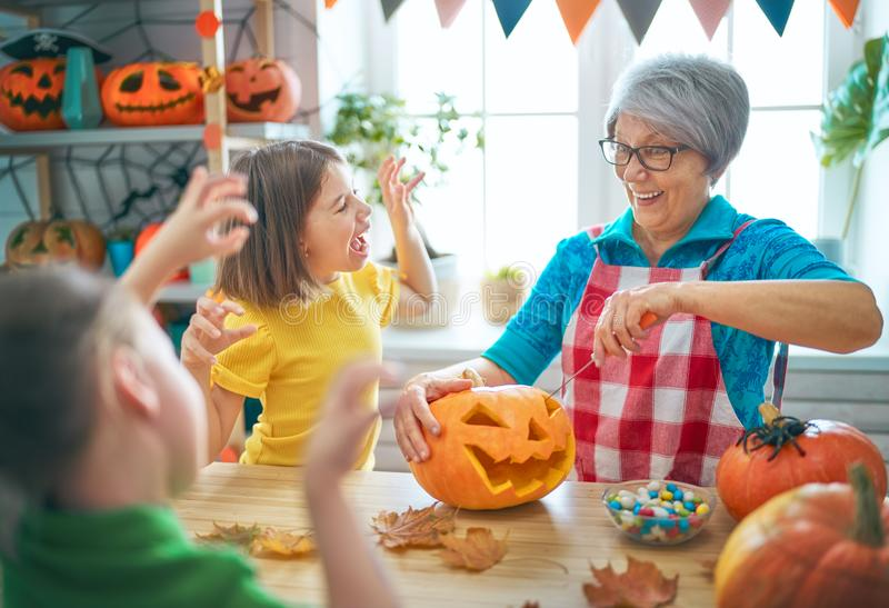 Family preparing for Halloween. Happy family celebrating Halloween. Grandmother, mother and children at home stock images
