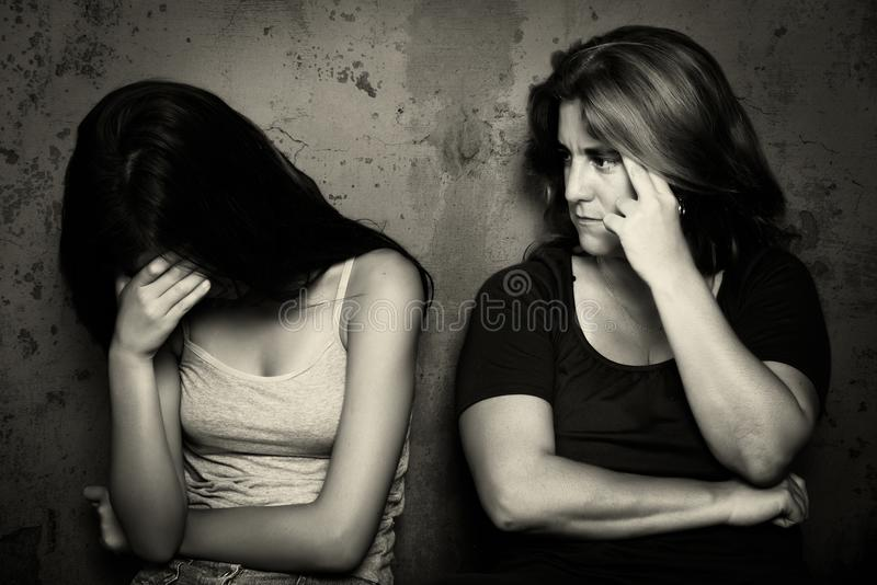 Teenage girl cries next to her angry and worried mother royalty free stock photo