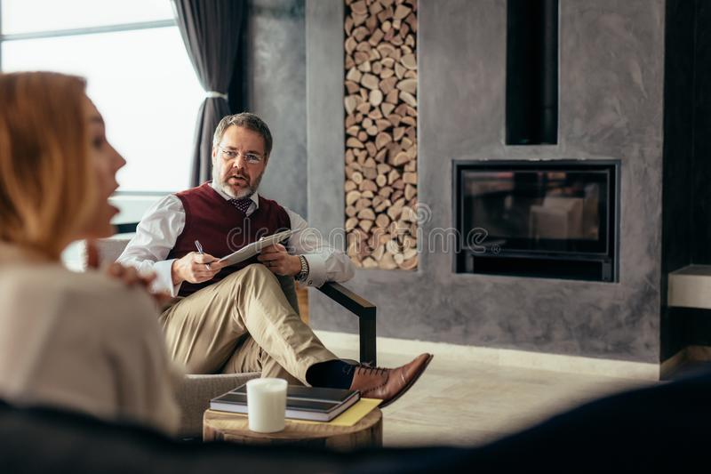Family psychologist consulting couple in trouble. Relationship consultant giving advice to couple at home. Family psychologist consulting couple in trouble stock photo