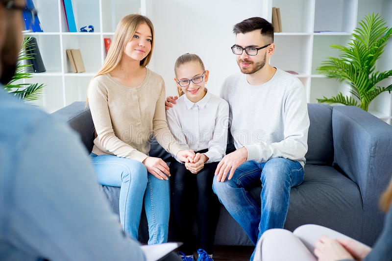 Family with psychologist. Family of three talking with psychologist. Psychologist taking notes stock photos