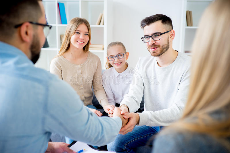 Family with psychologist. Family of three talking with psychologist. Psychologist taking notes stock photography