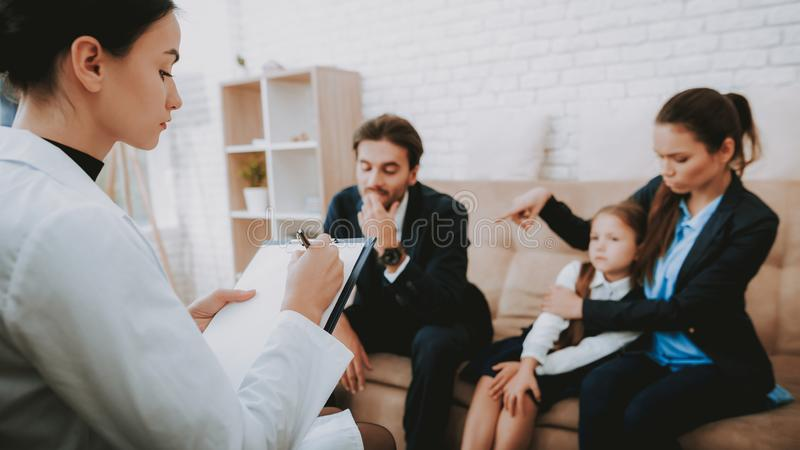 Family and Psychologist Writing Recommendations. Family in Bussiness Clothers. Happy Family. Psychologist in White Coat. Psychologist`s Office. Write stock photo