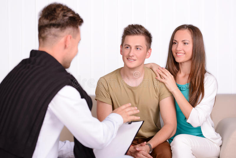 Family Psychologist. Young couple talking with family psychologist to solve their problems stock image