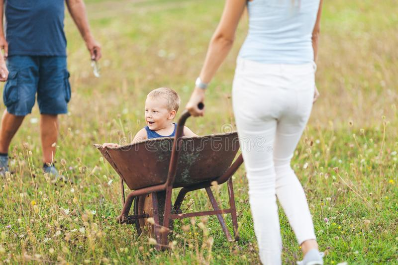Family pushing their small child in a wheelbarrow royalty free stock images