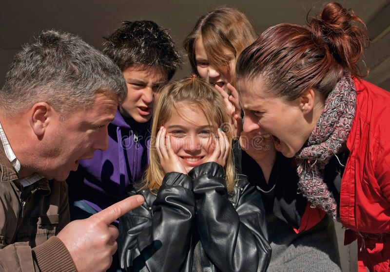 Family quarrel. The whole family (father, mother, brother and sister) off - yell and threaten a young girl with blond hair. She put her hands on his ears and royalty free stock image