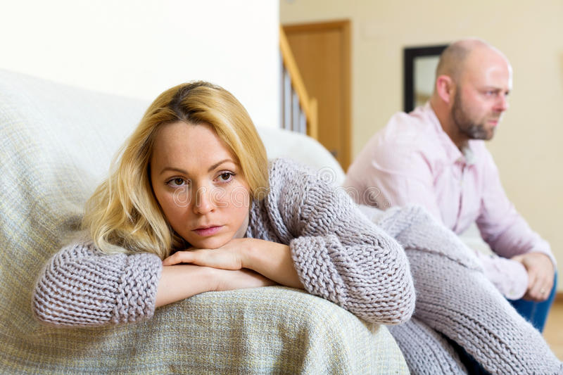 Family quarrel. Couple quarrel. Sad guy and wailful girl during quarrel in living room at home couple having problems at home royalty free stock images