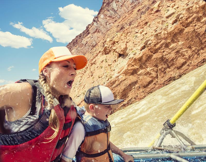 Family on a rafting trip down the Colorado River. Excited family riding the rapids in an inflatable raft down the scenic Colorado River near Moab, Utah and stock photos