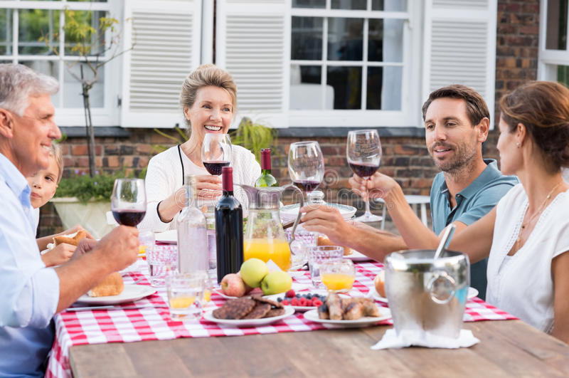 Family raising a toast. Happy family raising their glasses during lunch. Generation family toasting with red wine at picnic table. Parents with grandparents and royalty free stock images