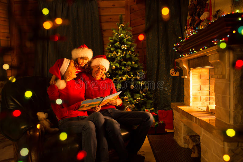 Family read Christmas book sitting on coach in front of fireplace in festive decorated house interior stock images