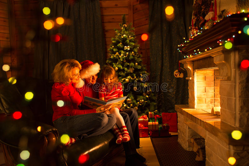 Family read stories sitting on sofa in front of fireplace in Christmas decorated house interior. Family read book sitting on sofa in front of fireplace in royalty free stock photos