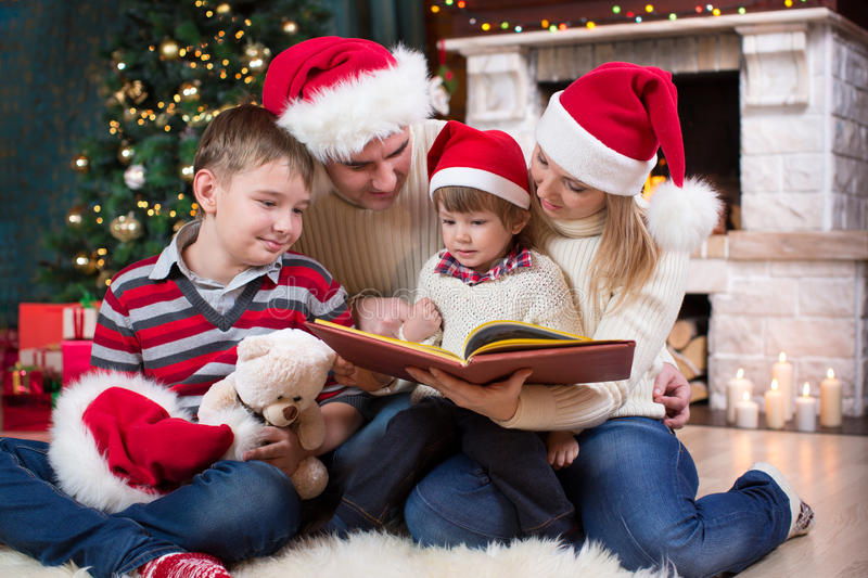 Family read stories sitting on sofa in front of fireplace in Christmas decorated house interior royalty free stock image