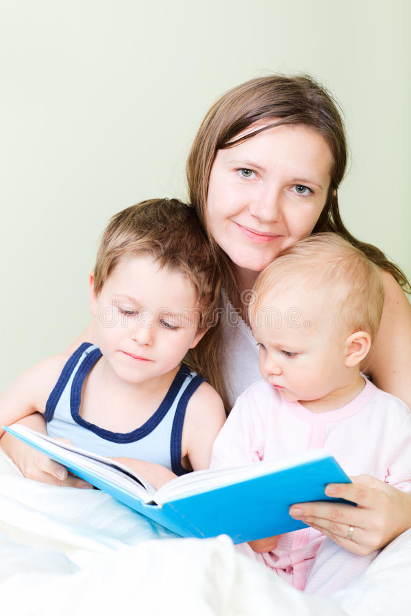Family Reading In Bed Stock Images