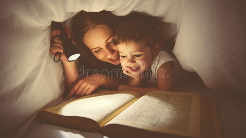 Family reading bedtime. Mom and child reading book with a flashlight under blanket. Family reading bedtime. Mom and child daughter reading a book with a