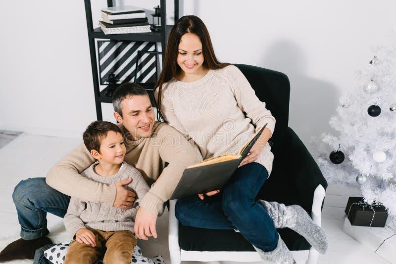 Family reading a book near Christmas tree stock photo