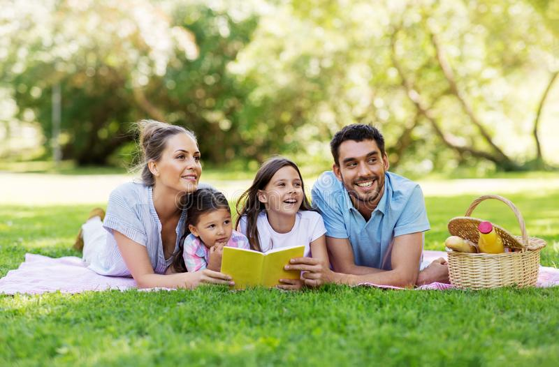 Family reading book on picnic in summer park stock photography