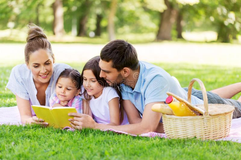Family reading book on picnic in summer park royalty free stock photo