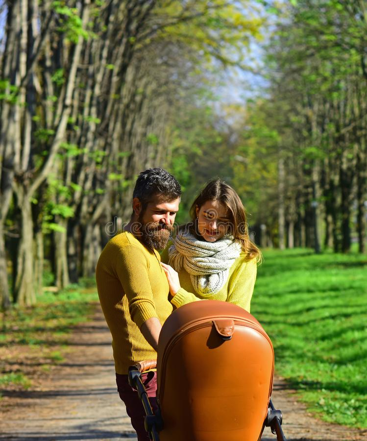 Family relations. Woman and man walk with baby pram in park, happy relations. The right relationship is everything. Family relations. Woman and men walk with stock image