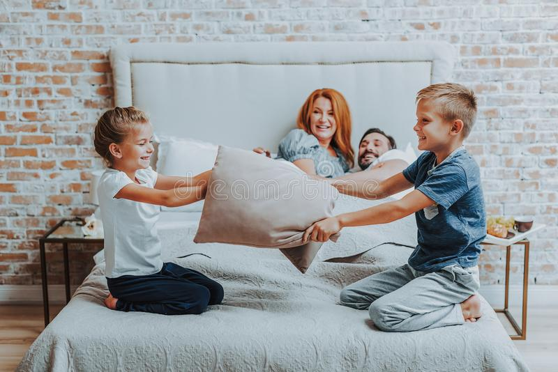Happy two children playing with pillow together stock photography