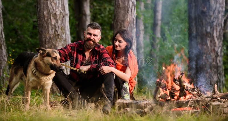 Family relax concept. Couple in love or young happy family. Spend time together. Woman, men and dog on vacation, hiking, camping. Couple with german shepherd royalty free stock images