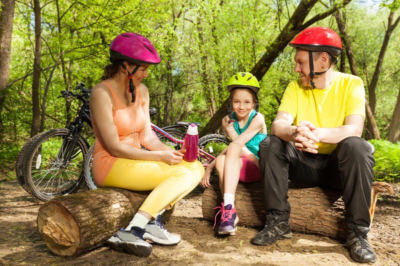 Family relaxing after cycling, sitting on the logs. Active family relaxing and drinking water from sports bottle after cycling, sitting on the logs royalty free stock images
