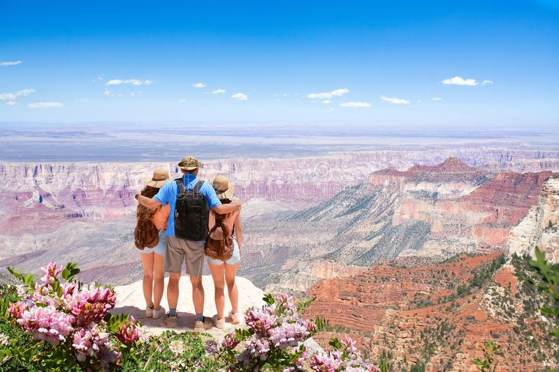 Family relaxing and enjoying beautiful mountain view on vacation hiking trip. Father with arms around his family. North Rim. Grand Canyon National Park stock image