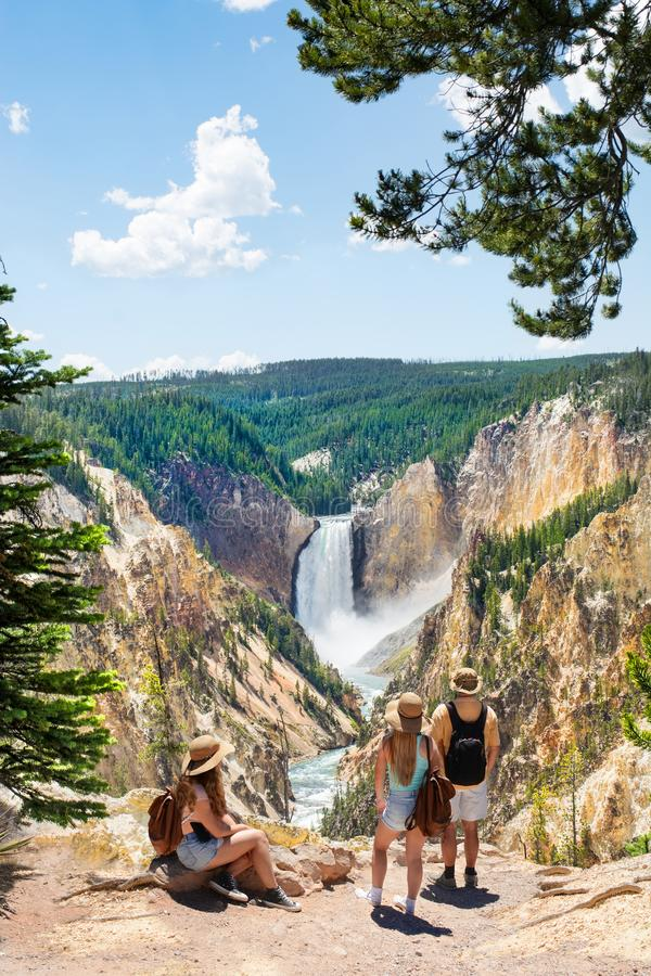 Family relaxing and enjoying beautiful view of waterfall on hiking trip in the mountains. Beautiful Lower Falls at Yellowstone National Park, U.S.A stock image
