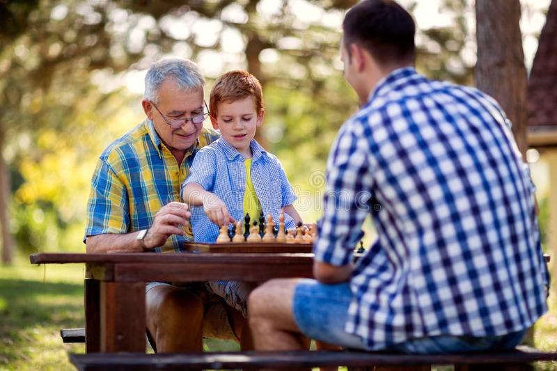 Family relaxing playing chess. In the park royalty free stock images