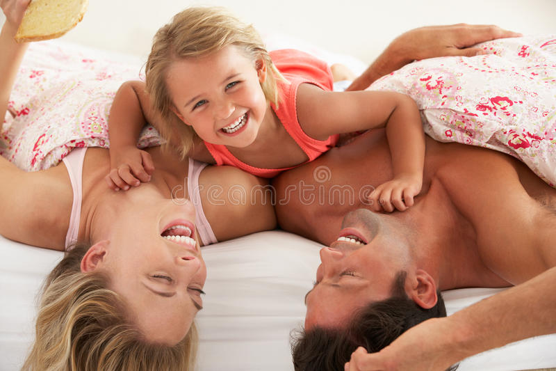Download Family Relaxing Together In Bed Stock Photo - Image of embracing, laughing: 26615834