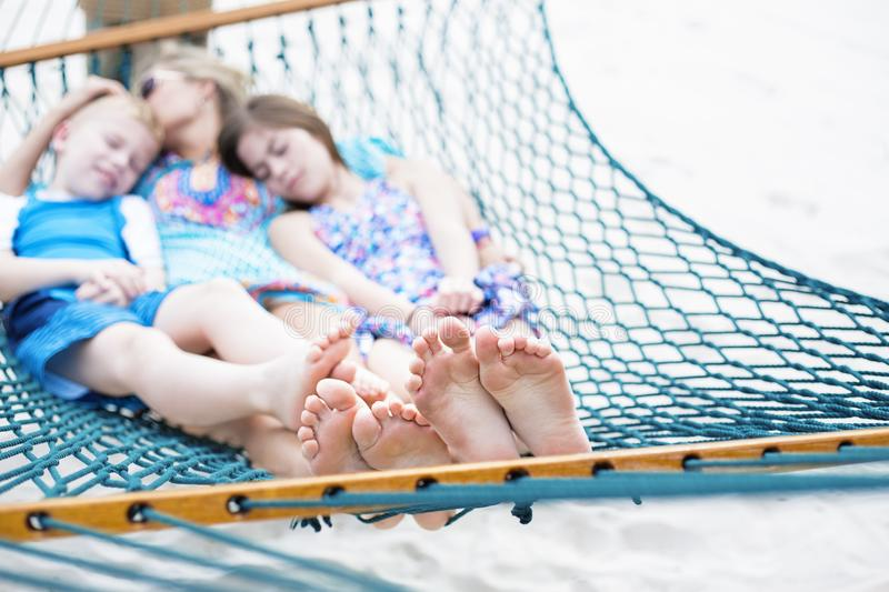 Family relaxing together on a hammock, focus on feet royalty free stock photography