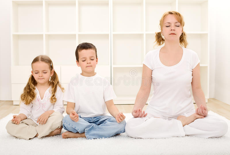 Family relaxing with yoga. Family - woman and kids - relaxing with yoga exercises indoors