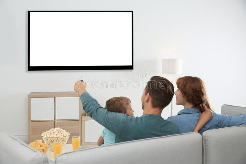 Family with remote control sitting on couch and watching TV at home, space for design on screen royalty free stock photography