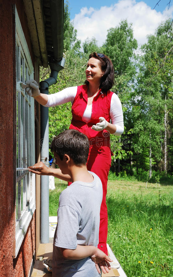 Family repairing house on the outside together stock photos