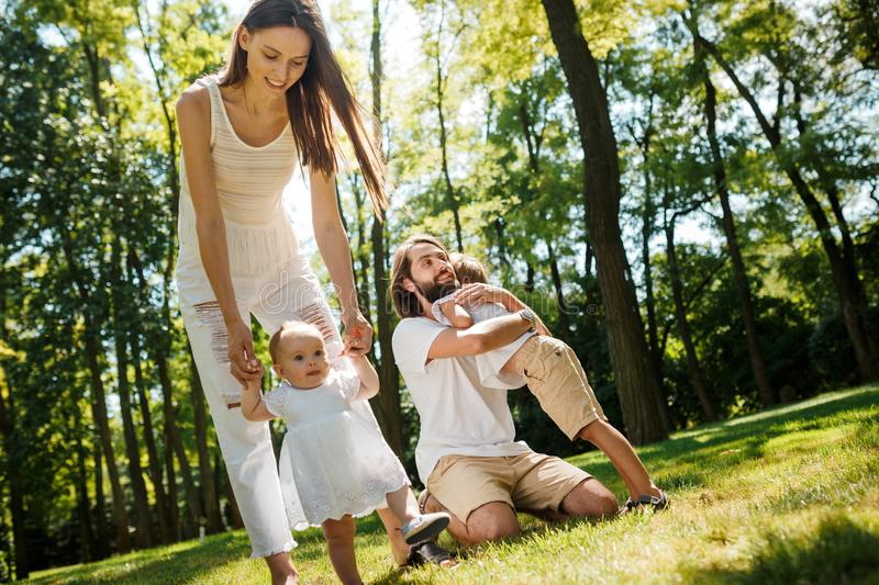 Family rest. Dark-haired mother and father dressed in white clothes are spending summer day with kids on a lawn in the stock photos