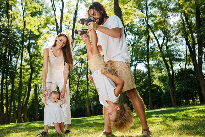 Family rest. Dark-haired mother and father dressed in white clothes are spending summer day with kids on a lawn in the stock image