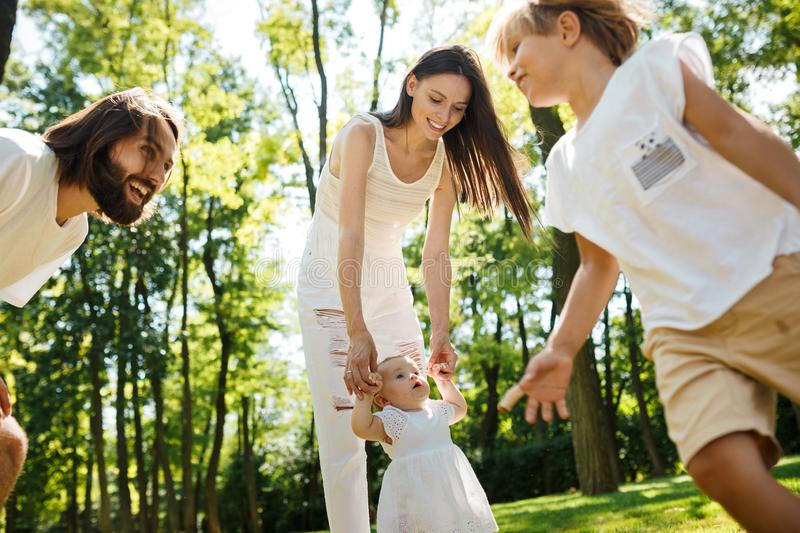Family rest. Dark-haired mother and father dressed in white clothes are spending summer day with kids on a lawn in the stock photography