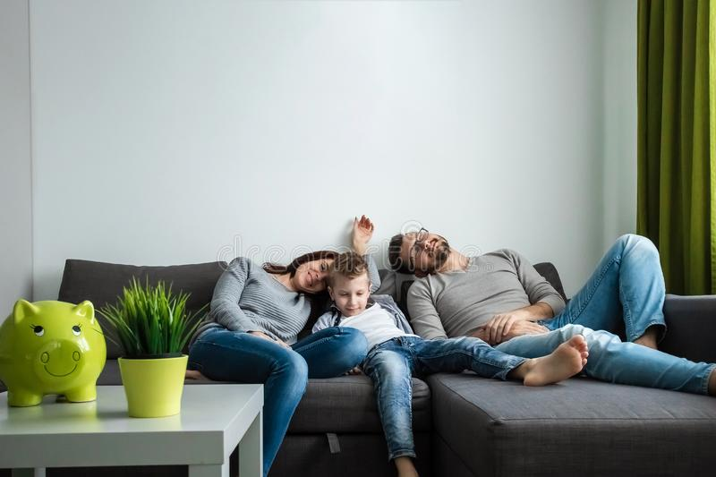 The family is resting on the couch all together. Concept of spending time together, happy family royalty free stock image