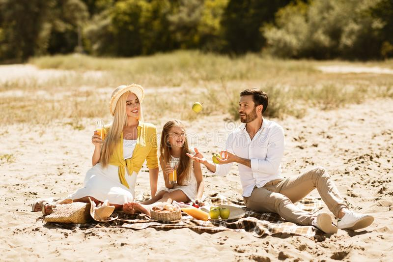 Family resting in nature, having picnic on blanket. Parents spending time with daughter stock image