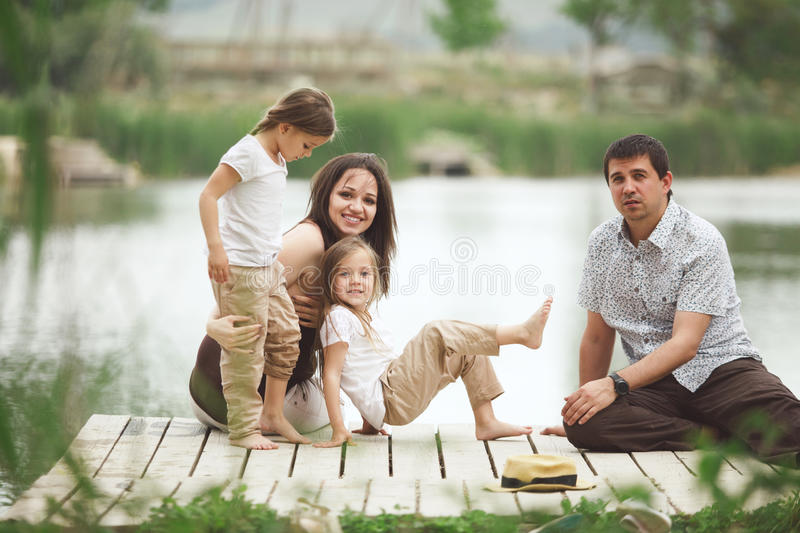Family resting near pond stock photography