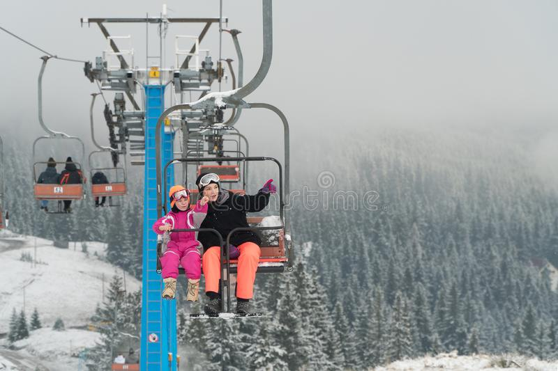 Happy family enjoying winter vacations in mountains . Mother with her daughter on the ski lift. royalty free stock image
